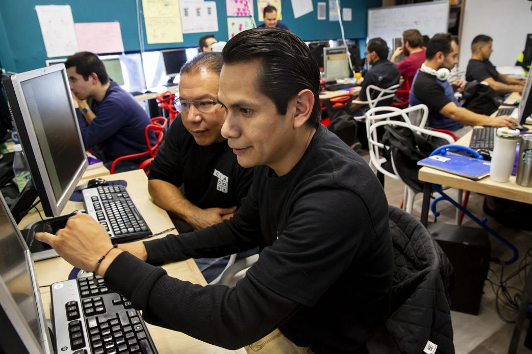 Orlando Mendoza works during classes of Hola Code, a nonprofit that offers training in software development for returnees and deportees in Mexico. Mendoza recently graduated from the program and secured a job. He grew up in Yakima and the Seattle area. Image by Erika Schultz. Mexico, 2019.