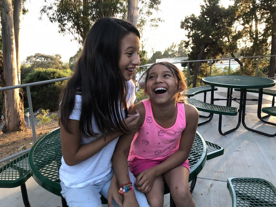 Adrianna and Cassandra share a laugh at Holy Names University. Located in the Oakland Hills, it's Camp Suzanne's home base. Image by Jaime Joyce for Time EDGE. California, 2018.