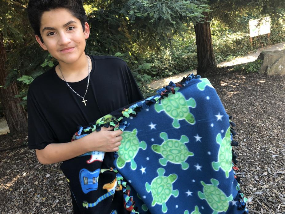 Carlos shows off a blanket he made with his mom. He chose the fabric with the guitars to reflect his love of music. His mom picked the sea turtles. Image by Jaime Joyce for TIME Edge. California, 2018.