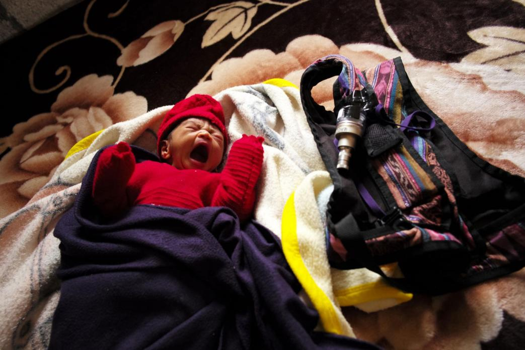 Dina Marroquín's eight-day-old baby rests next to a knapsack holding an indoor air monitor—part of study being done by an international research team to determine whether the use of gas stoves improves air quality and the health of children. Image by Lynn Johnson. Guatemala, 2017.