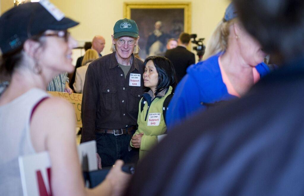 Duane Hanson and his partner Sally Kwan stand with others opposed to the New England Clean Energy Connect corridor project at the Maine State House in Augusta on June 4, 2019. Image by Michael G. Seamans. United States, 2019.