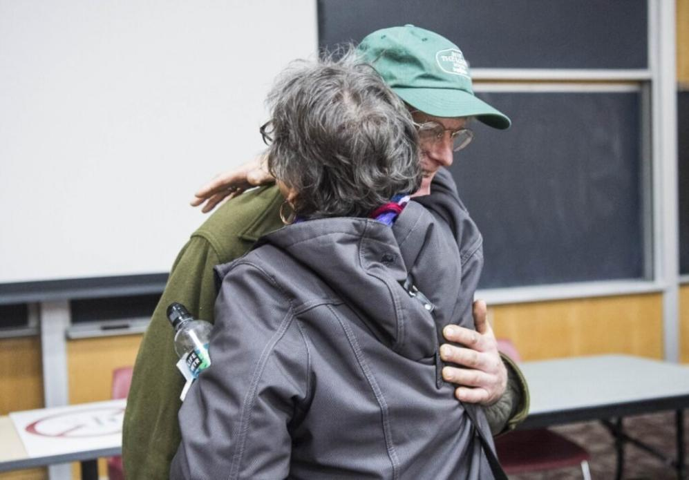 Duane Hanson embraces Roberta Benefiel-Frampton, director of the Grand River Keepers in Happy Valley-Goose Bay, Labrador, after a panel discussion at Preble Hall at the University of Maine in Farmington on Nov. 25, 2019. Image by Michael G. Seamans. United States, 2019.