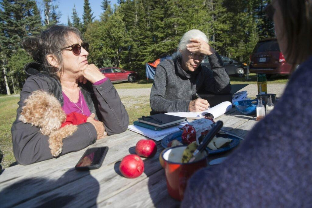 Roberta Benefiel-Frampton, left, discusses a plan for protesting the NorthEast Governors and Premiers meeting with Meg Sheehan, director of the North American Megadams Resistance Alliance, at New River Beach Provincial Park in Lepreau, New Brunswick, Canada, on Sept. 8, 2019. Image by Michael G. Seamans. Canada, 2019.