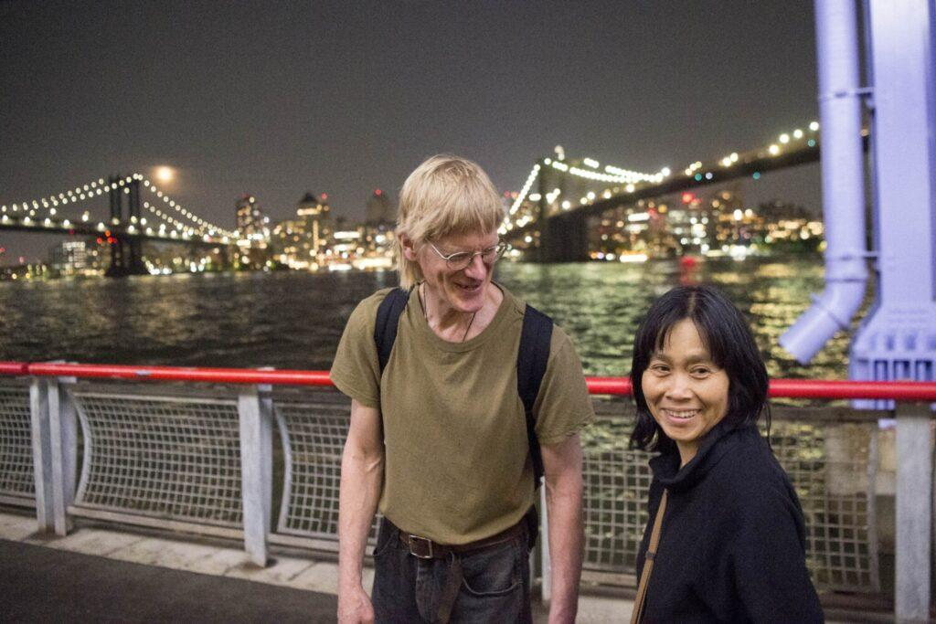 Duane Hanson, center, laughs with his partner Sally Kwan as they walk along the East River near Sally's childhood neighborhood in Chinatown, Manhattan, on May 19, 2019. Image by Michael G. Seamans. United States, 2019.