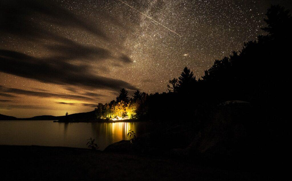 The night sky lights up over the Hanson/Kwan camp at Spencer Lake in T3 R5, in the Unorganized Territories of Maine, on Aug. 3, 2019. Image by Michael G. Seamans. United States, 2019.