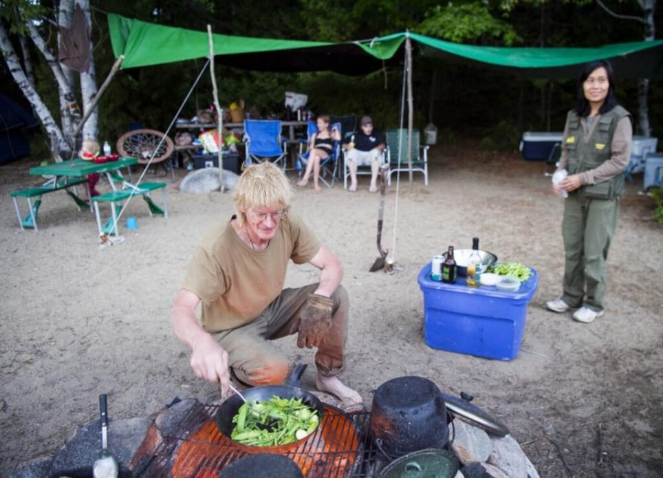 Duane Hanson cooks up vegetables grown at his homestead during the annual Hanson family camping trip at Spencer Lake in T3 R5, in the Unorganized Territories of Maine, on Aug. 3, 2019. Image by Michael G. Seamans. United States, 2019.