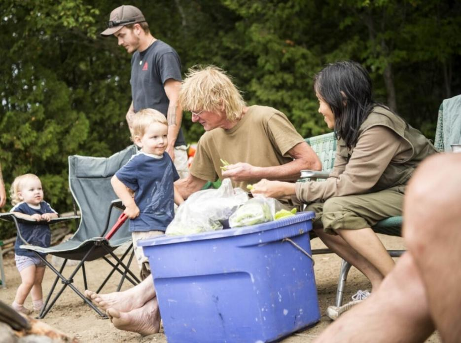 Duane Hanson greets his grandson, Jensen, while snapping green beans with Sally Kwan at Spencer Lake in T3 R5, in the Unorganized Territories of Maine, on Aug. 3, 2019. Image by Michael G. Seamans. United States, 2019.