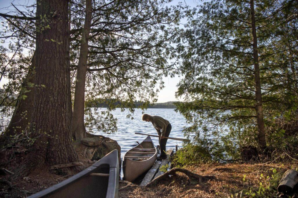 Duane Hanson prepares to launch one of his many canoes on to Whipple Pond at his homestead in the Unorganized Territories in the north woods of Maine near T5 R7 on May 26, 2019. Image by Michael G. Seamans. United States, 2019.