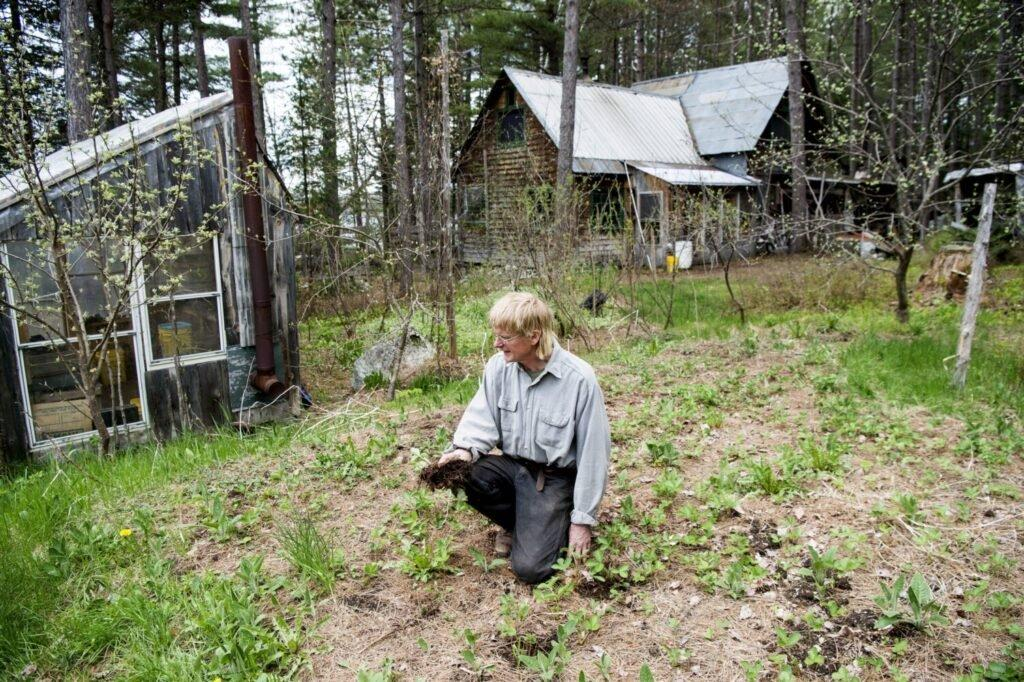 Duane Hanson checks the soil of his garden as prepares for the new growing season at his homestead in the Unorganized Territories in the north woods of Maine near T5 R7 on May 27, 2019. Image by Michael G. Seamans. United States, 2019.