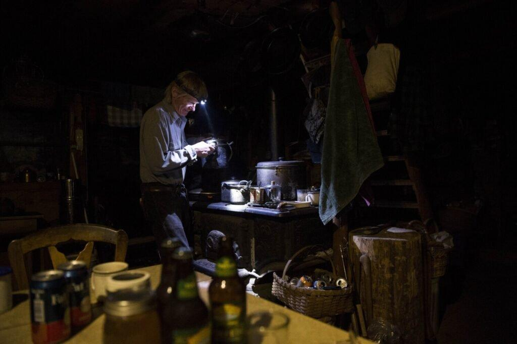 T5 R7, MAINE - MAY 26, 2019 Duane Hanson prepares dinner over his wood-fired stove at his homestead in the Unorganized Territories in the north woods of Maine near T5 R7 on May 26, 2019. Hanson has two solar panels and one light. Cooking over the stove by headlamp is not uncommon. Image by Michael G. Seamans. United States, 2019.