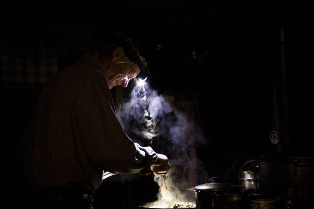 Duane Hanson prepares dinner over his wood-fired stove at his homestead in the Unorganized Territories in the north woods of Maine near T5 R7 on May 26, 2019. Hanson has two solar panels and one light. Cooking over the stove by headlamp is not uncommon. Image by Michael G. Seamans. United States, 2019.
