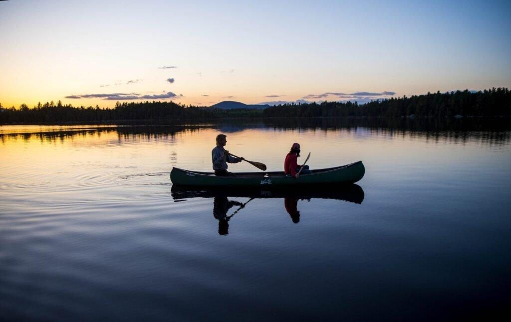 Duane Hanson and Sally Kwan paddle on Whipple Pond at their homestead in the Unorganized Territories in the north woods of Maine near T5 R7 on May 27, 2019. Image by Michael G. Seamans. United States, 2019.