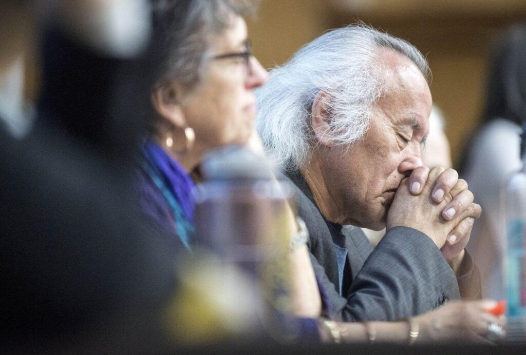 Tommy Monias from the Pimicikamak Territory in Manitoba, Canada, holds his head in his hands as a friend speaks about the impacts on their land from 'mega-dam' hydropower in Manitoba during a speaking tour at Preble Hall at the University of Maine in Farmington on Nov. 25, 2019. Image by Michael G. Seamans. United States, 2019.