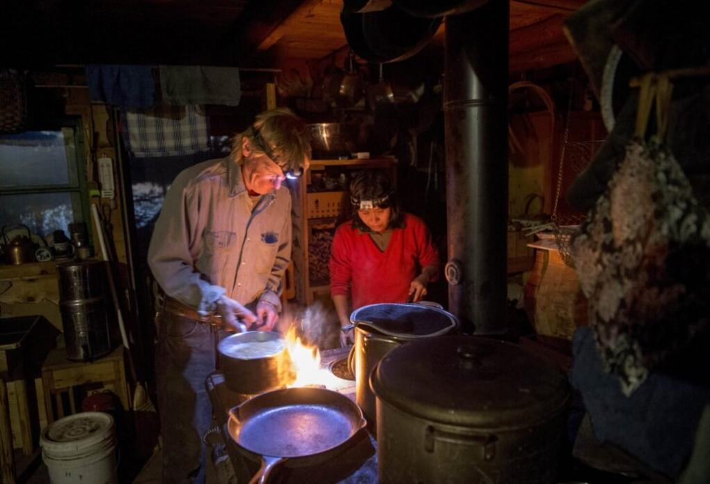 Duane Hanson and Sally Kwan prepare dinner at their home on Whipple Pond in T5 R7 in the Unorganized Territories of Maine on May 26, 2019. Using an antique wood stove, they cook dinner and heat the cabin. Image by Michael G. Seamans. United States, 2019.