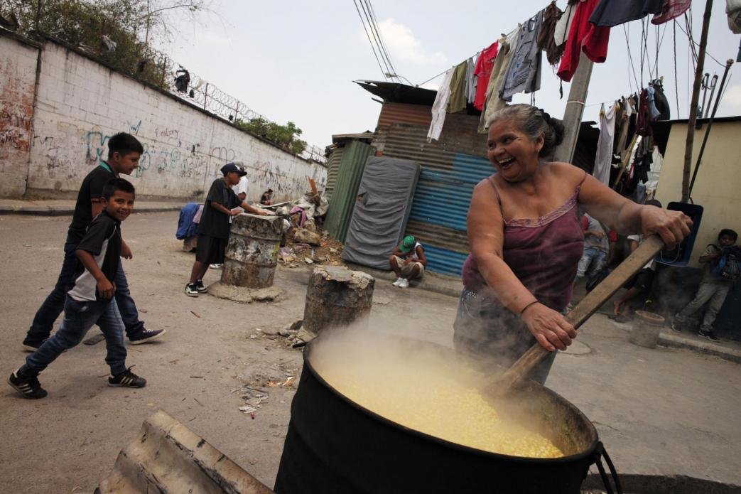 Alma Iris Garay, 50, who fled violence in El Salvador as a child, who has lost a son to drugs, beams as she stirs her vat of corn on a street corner, where the smoke from the open fire won't choke her. She makes tortillas on a gas stove inside her home in Guatemala City. Image by Lynn Johnson. Guatemala, 2017.