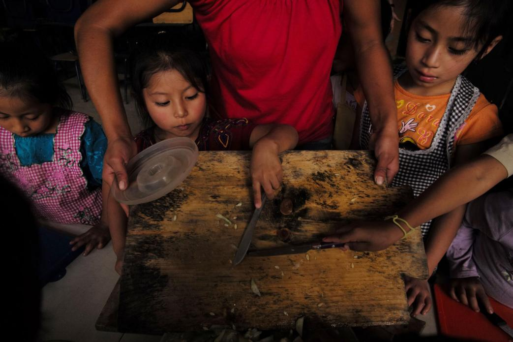 At Paso a Paso School in San Antonio Aguas Calientes, the kids make lunch with a stove made by the Ecocomal company, whose co-founder, Ana Luisa Herrera, also started the school. Safe, smokeless cook stoves promote education—because they help protect children's health. Image by Lynn Johnson. Guatemala, 2017.