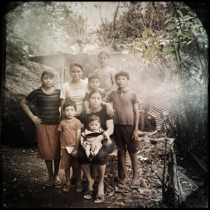Nancy López surrounded by her children. The family has an EcoComal plancha stove that is vented but they are surrounded by their neighbor's smoke. There is no escape. Image by Lynn Johnson. Guatemala, 2017.