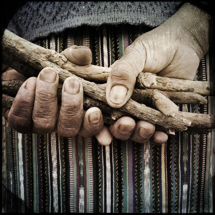 San Lorenzo: These are the hands of Juana Juarez Agustine, 63, holding wood that will be used to light a traditional chuj or sauna. Image by Lynn Johnson. Guatemala, 2017.
