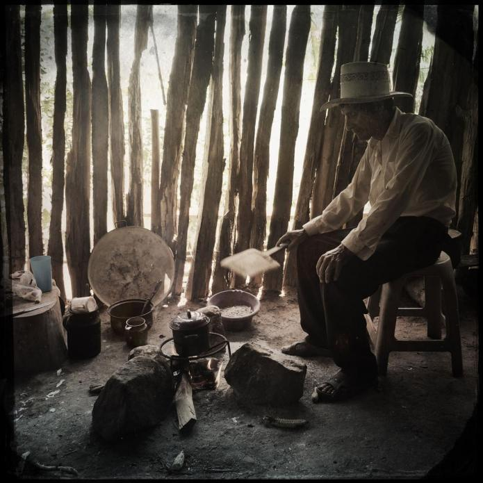 San Ramon: In a small town in southern Guatemala, an elderly man cooks over an open fire. He and his neighbors recently moved here from the Rio Squisal Valley, near the border with Mexico, in search of better farmland. Image by Lynn Johnson. Guatemala, 2017.