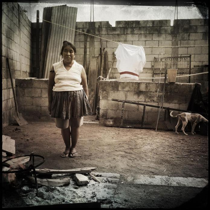 San Antonio Aguas Calientes: Maria Ermelinda Lopez Mendoza stands in her cooking area in her courtyard. She can't afford a stove, so she cooks over this makeshift open flame. Image by Lynn Johnson. Guatemala, 2017.