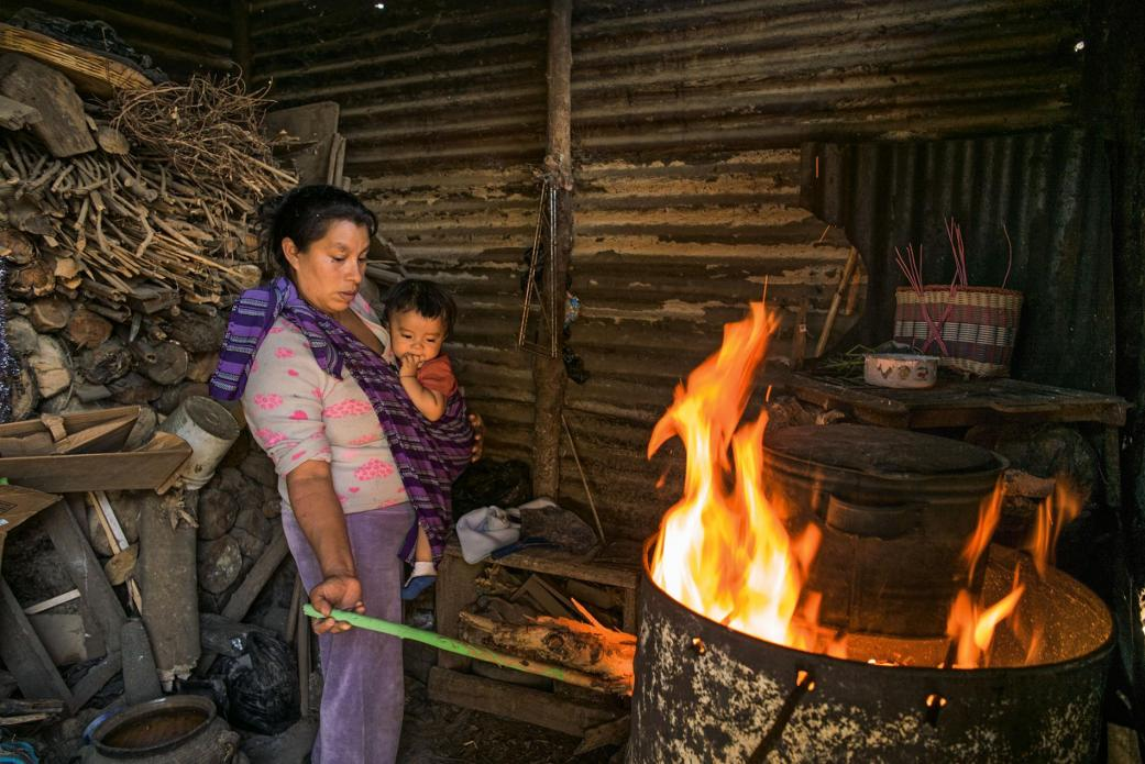 Near Antigua Guatemala, eight-month-old Pablito keeps an eye on breakfast as his mother, Angélica Epatal Garcia, tends to the makeshift barrel stove. She and her daughters walk 45 minutes each way to collect the wood for three daily fires. Image by Lynn Johnson. Guatemala, 2017.
