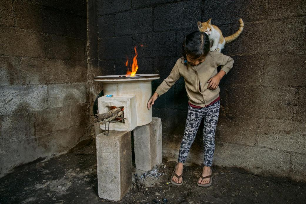 Tania López, seven, plays with her cat in a room whose walls were blackened by an old open fire; the new stove, provided by StoveTeam International, is efficient and safe to touch. Image by Lynn Johnson. Guatemala, 2017.