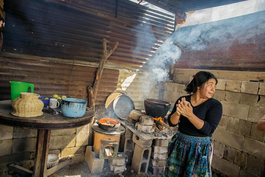 The new yellow stove is efficient, but the old open fire is better for the giant pot in Etelvina Pérez's kitchen in San Antonio Aguas Calientes. Image by Lynn Johnson. Guatemala, 2017.