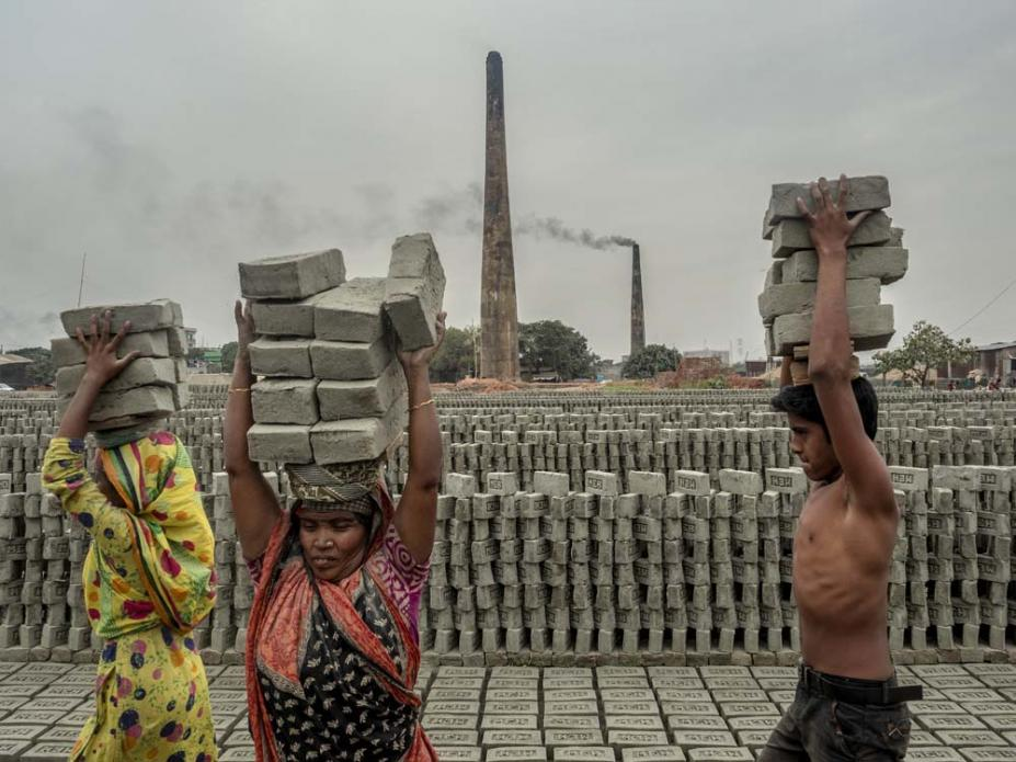 Workers carry bricks after they are formed and stack them in preparation for firing. Roughly one million people are employed in Bangladesh's brickmaking facilities, which generate nearly 60 percent of the particulate pollution in Dhaka. Image by Larry C. Price. Bangladesh, 2018.