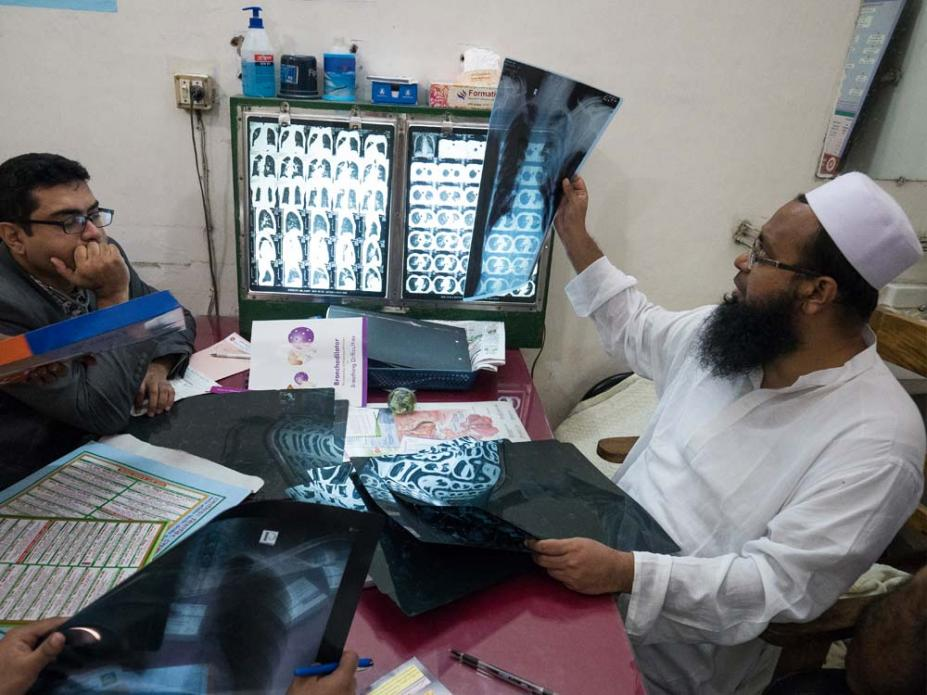 "Dr. Ferdous Wahid, right, examines a chest x-ray. ""This makes me alarmed,"" one Dhaka resident said of the city's pollution, ""thinking how much of the dust is settling in my lungs."" Image by Larry C. Price. Bangladesh, 2018."