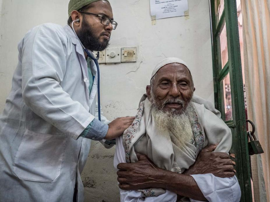 A lung specialist listens to the raspy breathing of a patient. Dr. Wahid says asthma is the most common pollution-related disease he sees. Image by Larry C. Price. Bangladesh, 2018.