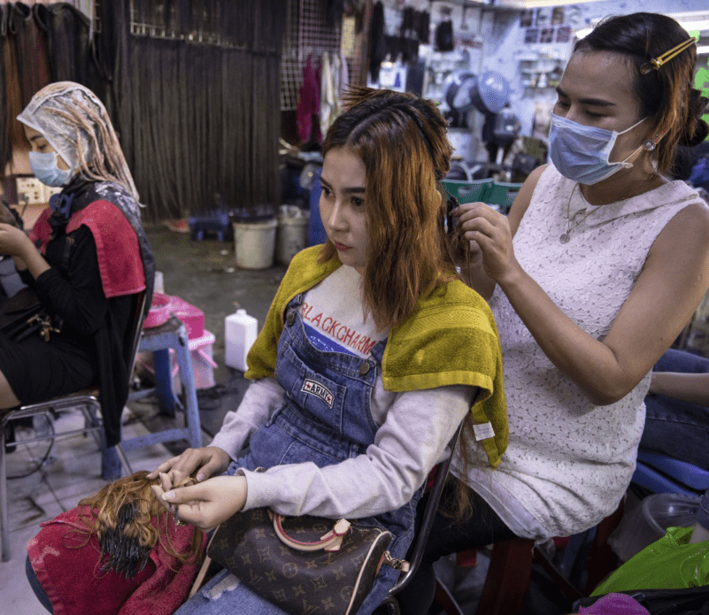 Hair salon owner Meyly Heng places a hair extension on a customer in Phnom Penh. Image by Paula Bronstein. Cambodia, 2019.