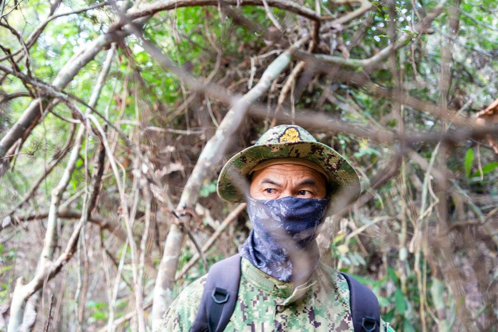 A Cambodian environmental ranger on patrol looking for illegal loggers in the Phnom Tnout Phnom Pok sanctuary. Some rangers hide their identity out of fear of reprisals from loggers and their allies in the police and military. Image by Sean Gallagher. Cambodia, 2020.<br />
