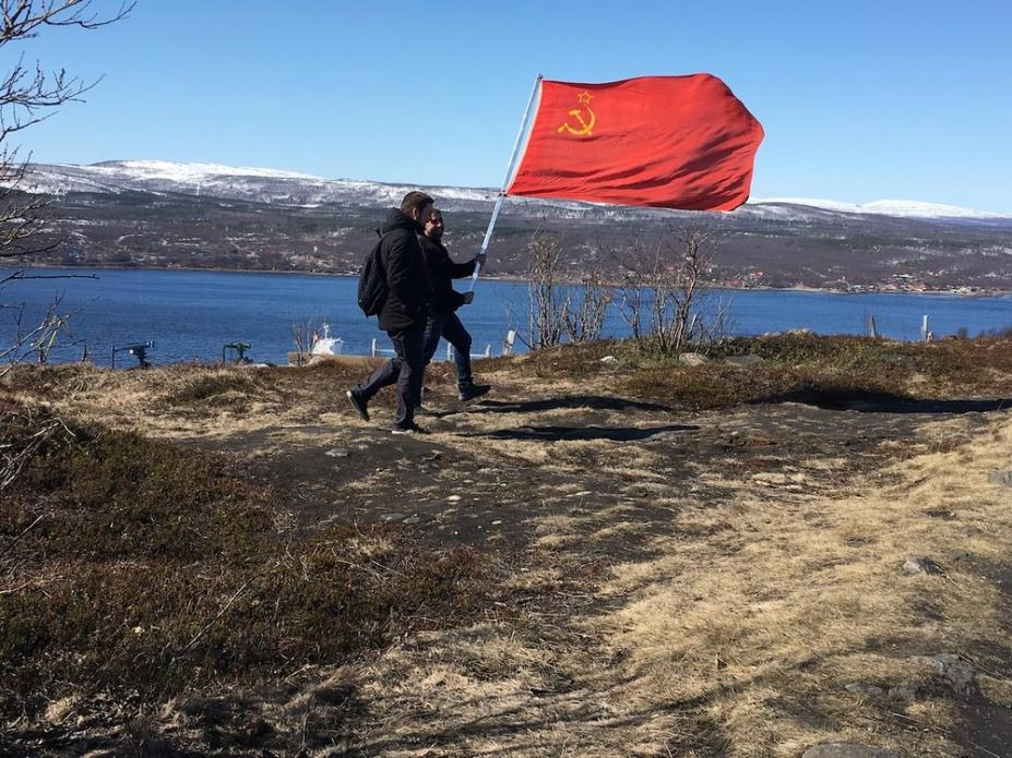 Two men carry a Soviet flag Murmansk, Russia. Image by Amy Martin. Russia, 2018.