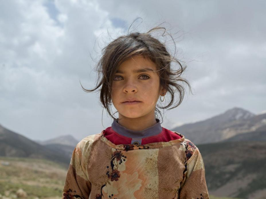 Marzieh Seyfouri, eight, and her family just arrived from Khuzestan Province to find grass and water on Zard Mountain to feed their flock. She doesn't like her family's tent but loves attending school in Khuzestan. Image by Newsha Tavakolian. Iran, 2018.