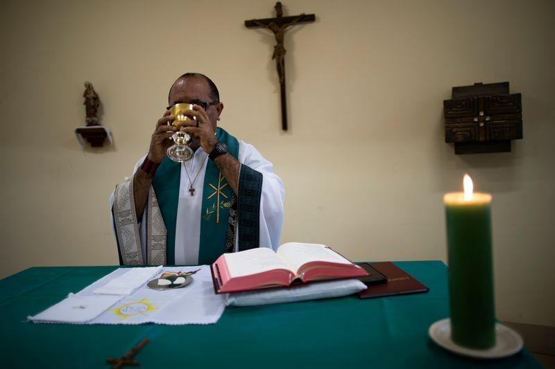 Father Amaro Lopes partakes in the sacrament while celebrating a mass in a chapel at the bishop's house in Altamira. Image by Spenser Heaps. Brazil, 2019.