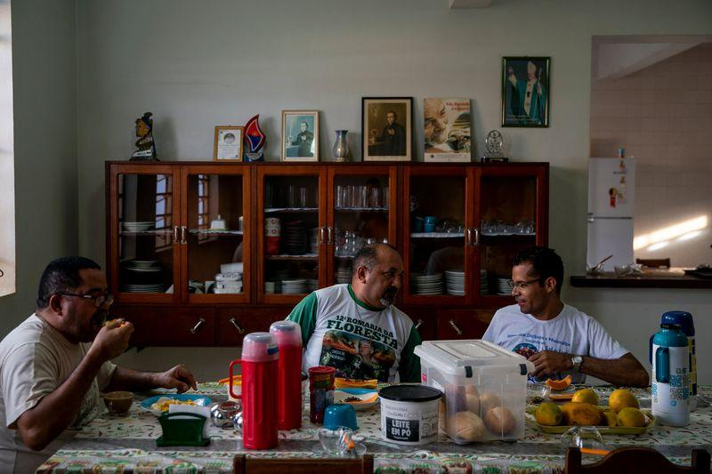 Father Amaro Lopes, center, eats breakfast with others at the bishop's house in Altamira. Image by Spenser Heaps. Brazil, 2019.