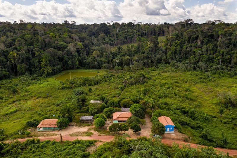 The home of Elias da Silva Lima and his family, center, and a school, left, are pictured in the Virola Jatoba settlement in Anapu. Image by Spenser Heaps. Brazil, 2019.