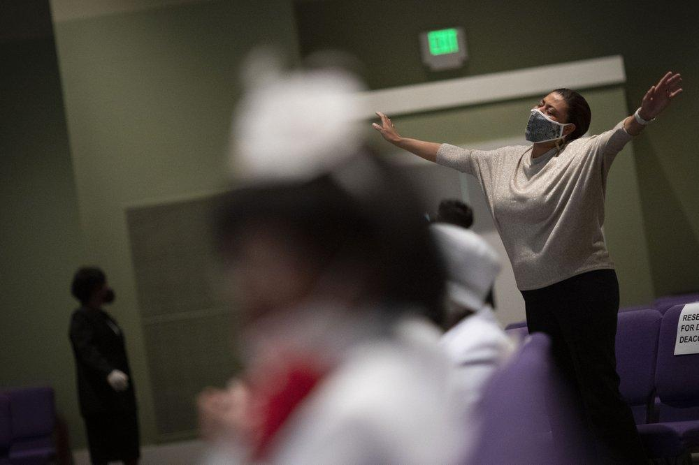 A woman wearing a face mask prays during a church service at the New Horizon Church International. Image by Wong Maye-E/AP Photo. United States, 2020.