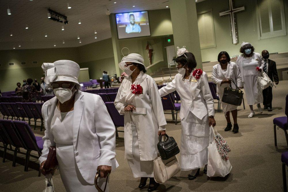 Women wearing face masks leave after a church service at the New Horizon Church International. Image by Wong Maye-E/AP Photo. United States, 2020.