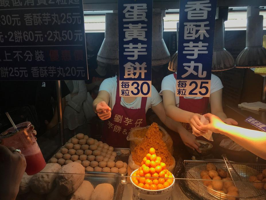 This stall sells taro fritters. In front is a pyramid of egg yolks used in the fritters. Image by Melissa McCart. Taiwan, 2018.
