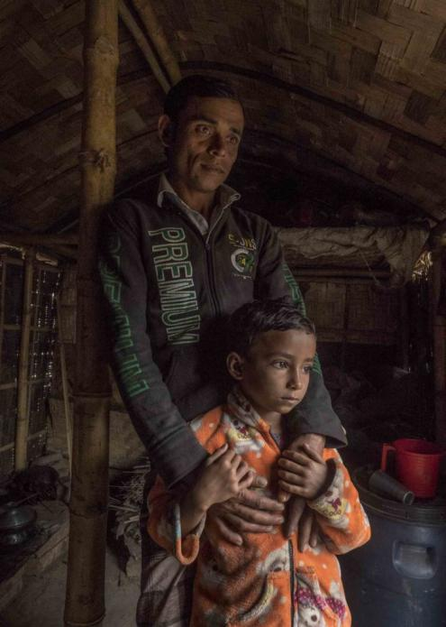 Workers like Mohammad Esarul Molla, 28, and his daughter Moumita, age 6, reside in huts on the factory property. While the air is often hard to breathe, the job is welcomed. Image by Larry C. Price. Bangladesh, 2018.