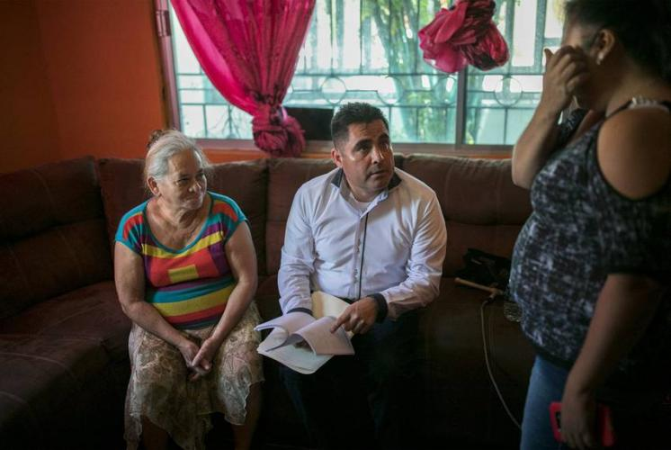 Immigration lawyer Eduardo Beckett sits next to his client, Bertha Arias, as he speaks to Elena, the owner of the safe house where Arias stays in Ciudad Juárez. Image by Ivan Pierre Aguirre. Mexico, 2019.