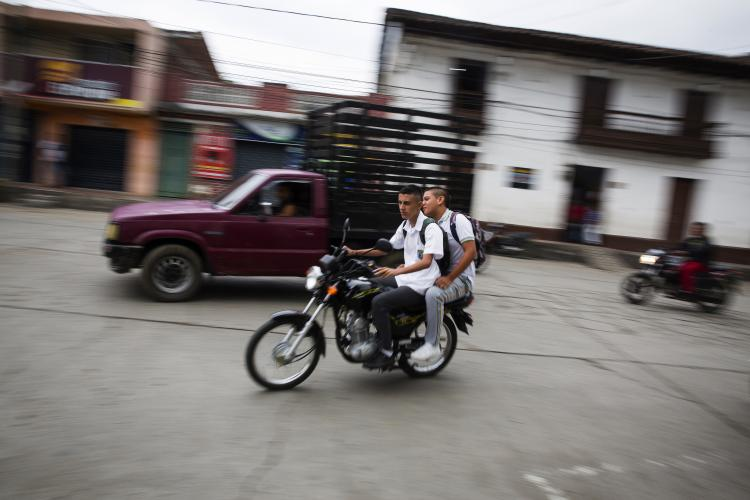 Young men on a motorcycle pass through the central town square in La Union, Colombia on Tuesday, March 6, 2018. Image by Greg Kendall-Ball. Colombia, 2018.