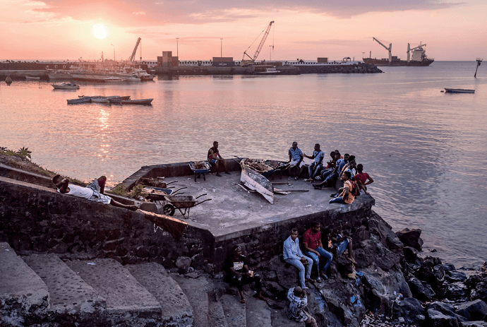Comorians resting on the waterfront in Moroni, the capital of the Union of the Comoros. Image by Tommy Trenchard. Comoros, 2019.