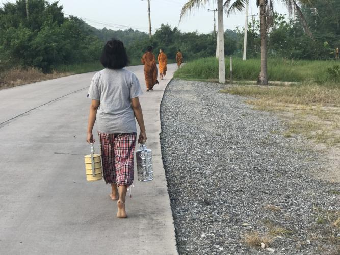 A young Thai girl follows three novice monks in the collection of the morning alms, during which they accept donations of food and drink to the temple from residents throughout the village of Chonburi. Image by Kiley Price. Thailand, 2018.