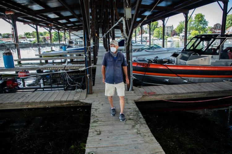 Navy Point Marine co-owner Peter Leubner walks his docks at Sackets Harbor, New York, on July 31, 2020. In 2017, he said, he was forced to shut down the power to the marina as waves crashed in and 35 boat slips were lost. Image by Zbigniew Bzdak/Chicago Tribune. United States, 2020.<br />