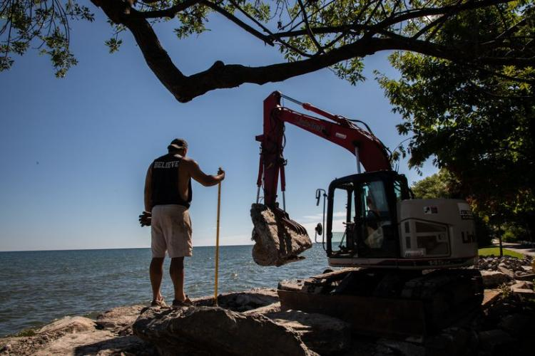 Workers reinforce a rock wall in front of a residential house on the shore of Lake Ontario in Greece, New York, on July 28, 2020. Image by Zbigniew Bzdak/Chicago Tribune. United States, 2020.