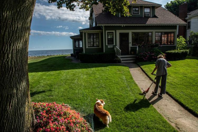 Nancy Sullivan, with dog Carter, tends to her house along the shore of Lake Ontario in Greece, New York, on July 30, 2020. She has lived at this house for the past 55 years and recently spent some of her retirement money to repair her seawall. Image by Zbigniew Bzdak/Chicago Tribune. United States, 2020.<br />
