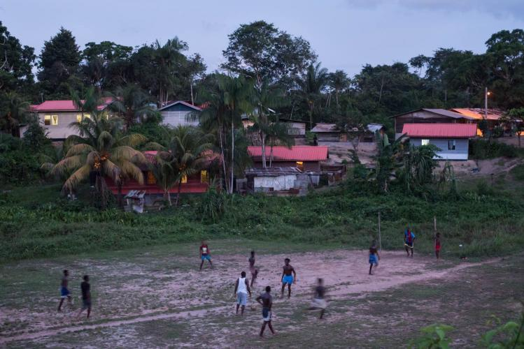 People play soccer as dusk falls on the village of Adjuma Kondre in Suriname. The village's water sources have been impacted by Alcoa's nearby mining operations. Image by Stephanie Strasburg. Suriname, 2017.