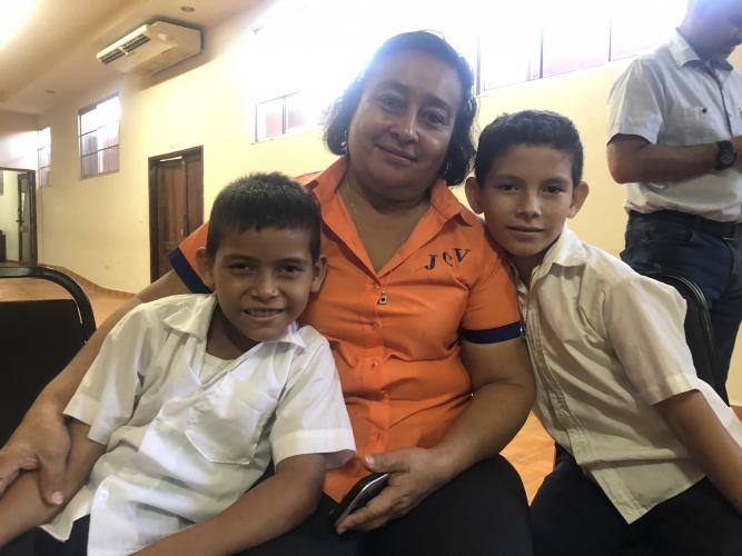 Berkling Yaiso (left) is 9. His brother Germán is 10. Here, at a community meeting in Potrerillos, they pose with one of their teachers. Image by Jaime Joyce/TIME for Kids. Honduras, 2019.